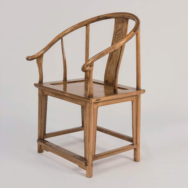A pair of China chairs in elm and bent, laminated, and lacquered mahogany. Medallion carved into the back vertical rail.