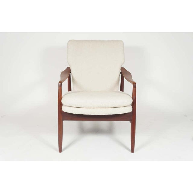 A very sleek and elegantly designed Kofod-Larsen easy chair with new nubby cream colored upholstery and solid teak frame....