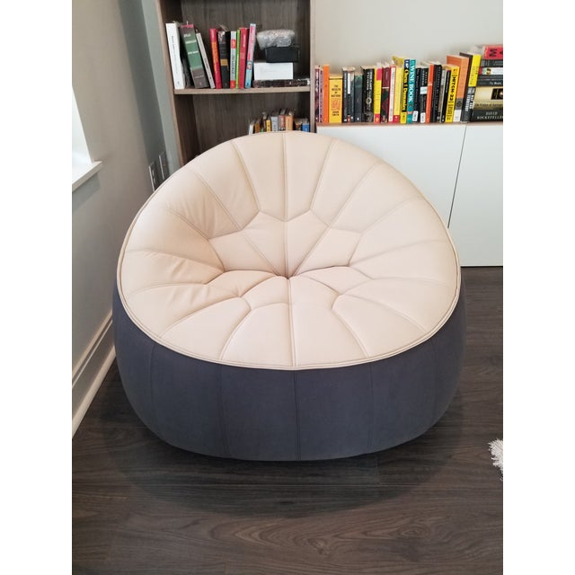 Authentic Ligne Roset Ottoman armchair. Barely used, the chair features a swivel base with two-tone upholstrey in beige...