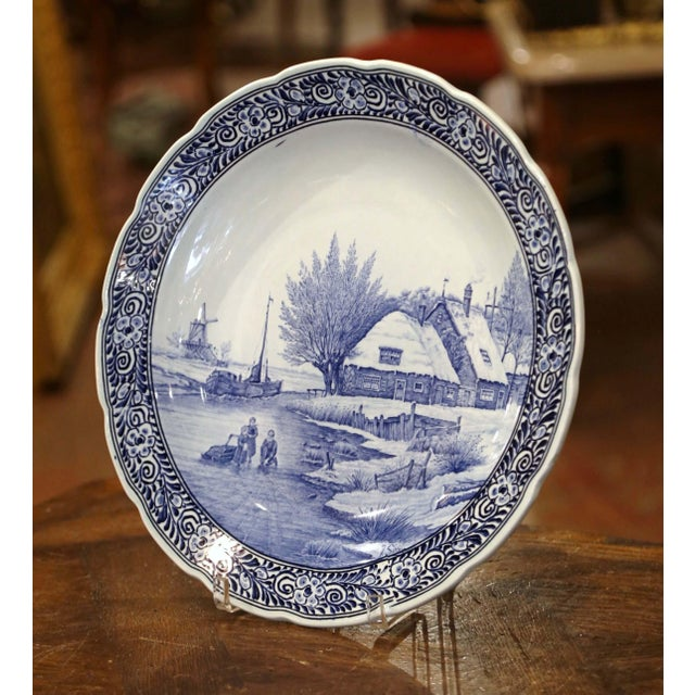 This large antique charger was crafted in Holland, circa 1960. The large, wall hanging plate depicts a wintry cottage...