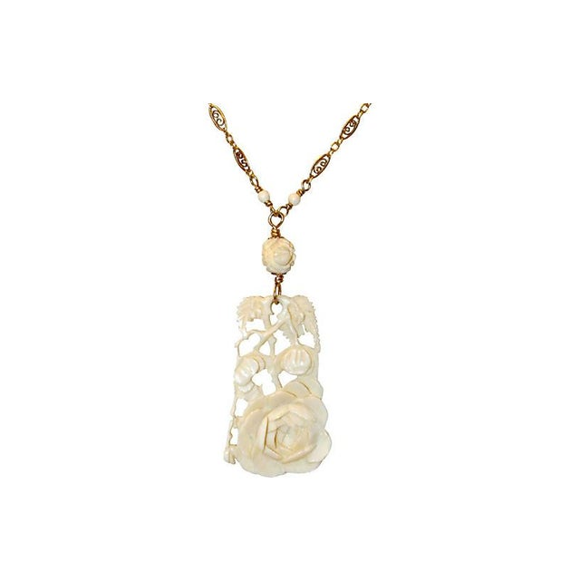 1920s carved bone floral pendant hanging from a finely detailed gold-filled and bone bead replacement chain. Pendant,...