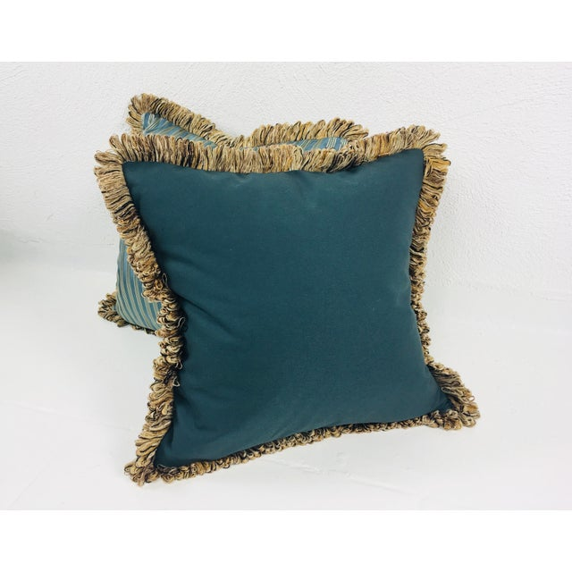 This is a pair of Coraggio teal & silver striped pillows with cotton reverse and brush fringe trim. Pillows are made in...