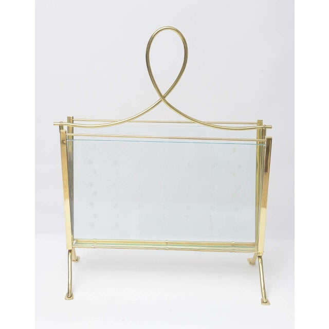 A glamorous and refined 1940s Italian magazine rack. A polished brass frame holds cut-glass side panels, etched with a...