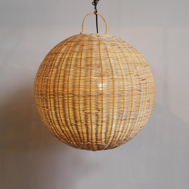 Hand woven raw rattan globe lantern. Each may have slight variations in handmade detail and natural tones.