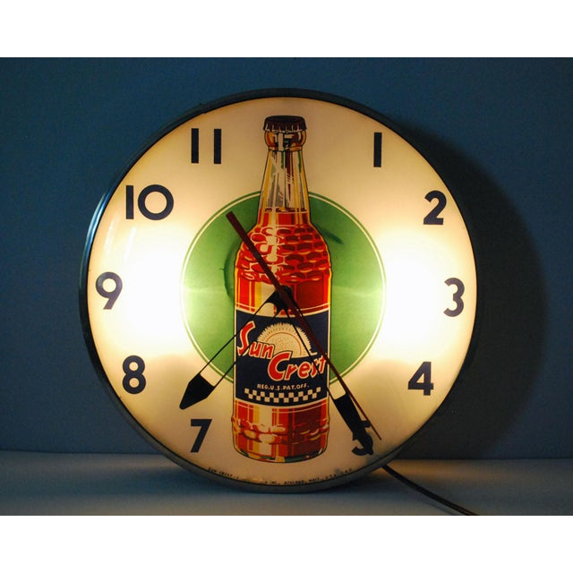 Fun vintage light up advertising wall clock for Sun Crest soda pop, with a large orange soda bottle on a lime green...