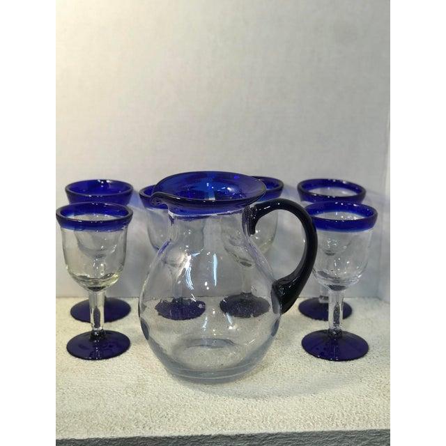 "Vintage hand blown Mexican glass cobalt blue trim pitcher with 6 matching goblets. Pitcher dimension 8""w 6.5""d 10""h..."