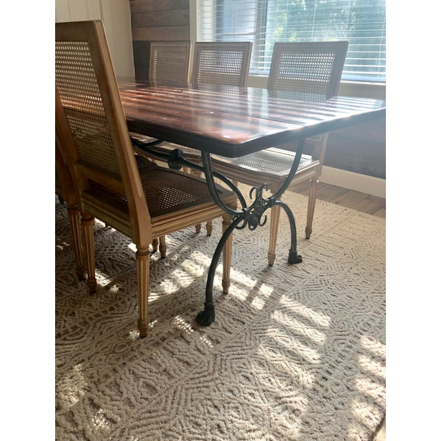 Gorgeous and timeless large wood dining table by Theodore Alexander. Accented with a metal clawfoot base. Marked on the...