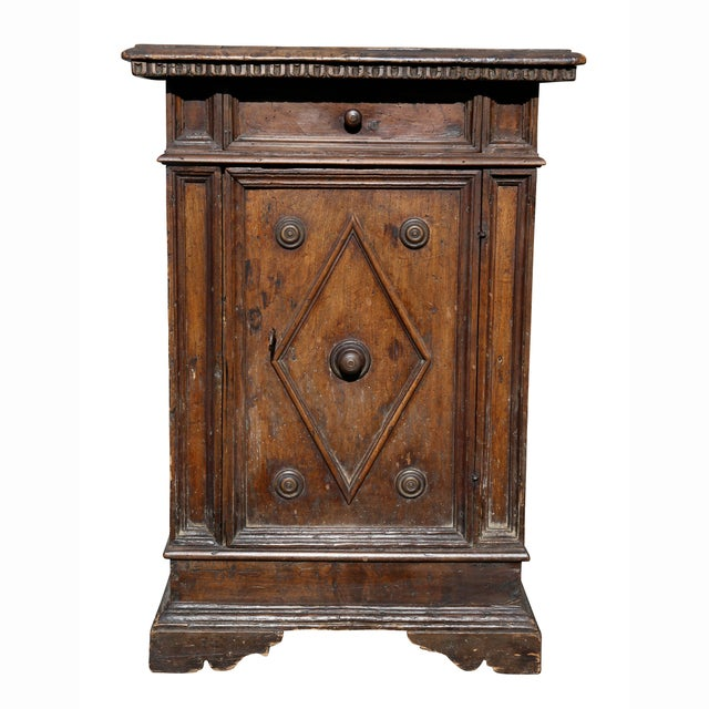 Rectangular top over a drawer and a door with a diamond shaped molding with four roundels, bracket feet.