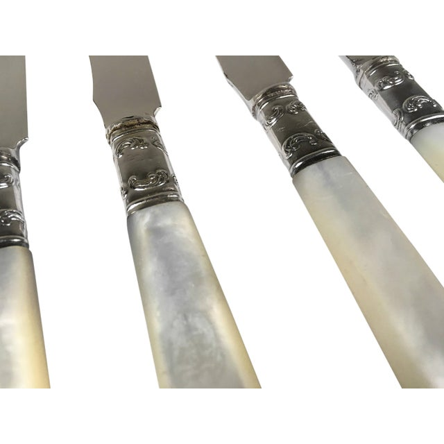 Offering a set of 8 sterling silver and mother of pearl knives with silver plated blades. The handle collar is stamped...