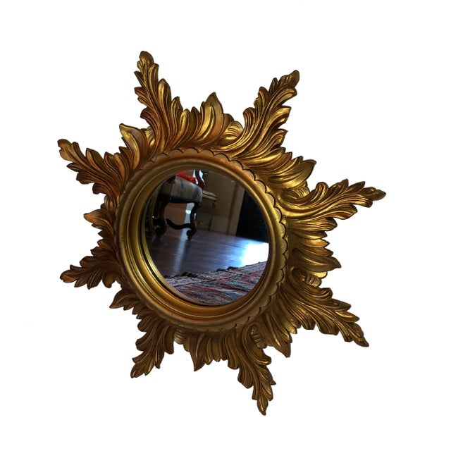 A round mid century starburst mirror in gold from Italy. Perfect for using in any room or grouping with other starburst...