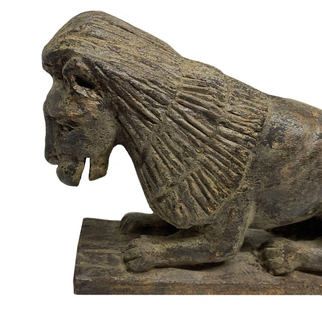 This is a fine carved naive sculpture depicting a recumbent lion. The lion is robustly carved with an expressive face and...