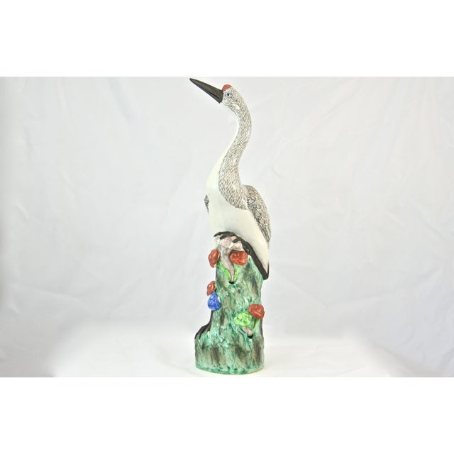 Tall 16 inch antique white ceramic crane or water bird with finely hand painted textural details standing on a green...