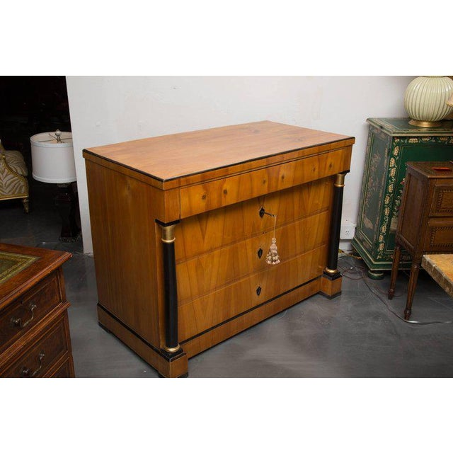 This is a sophisticated example of a fine Biedermeier cherrywood chest of drawers. The plank top is framed by ebonized...