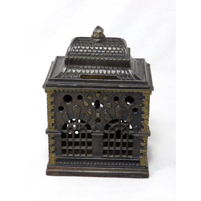 An American Victorian cast iron coin bank in the Form of a bank building. It has nice all original painted features. Circa...