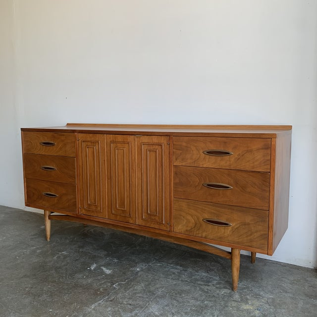 Vintage Sculptra low triple dresser manufactured by Broyhill in walnut. This piece features the line's signature cat eye...