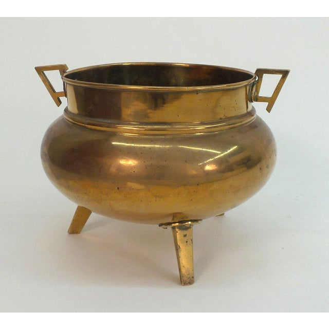 An English Aesthetic movement brass tripodal coal skuttle, now