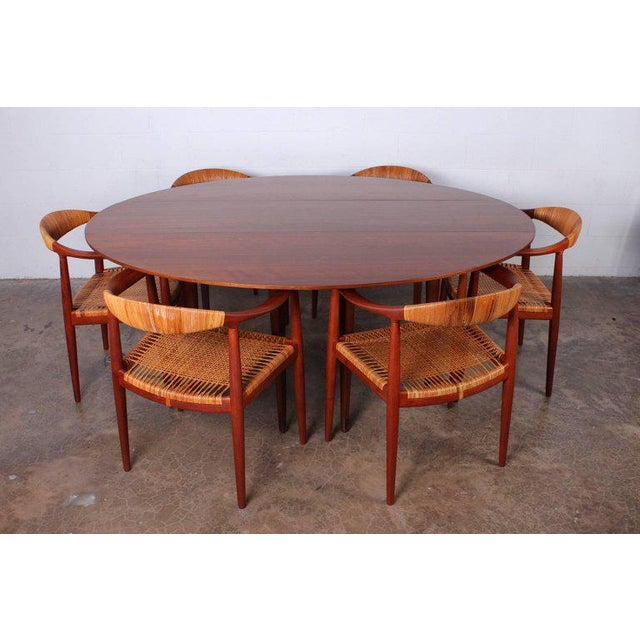 A beautiful and versatile drop-leaf console/dining table designed by Edward Wormley for Dunbar. Walnut with leather sabots...