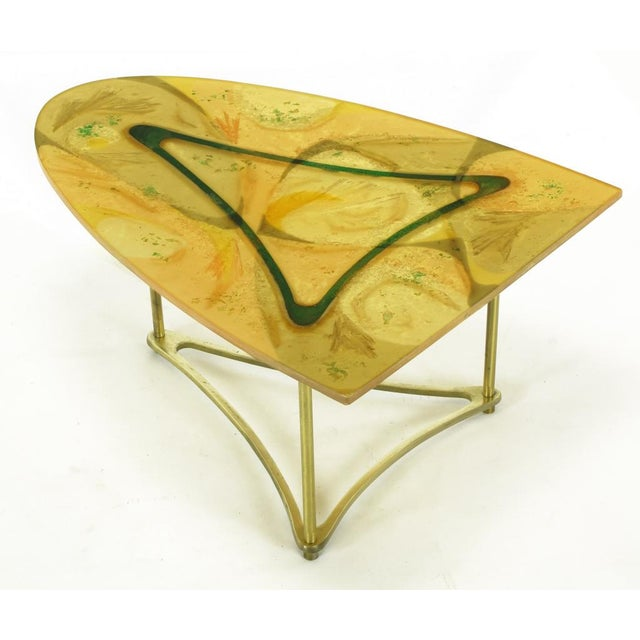 One third surf board shaped side table on triangular brass base. Three brass legs attach the triangular brass base to the...