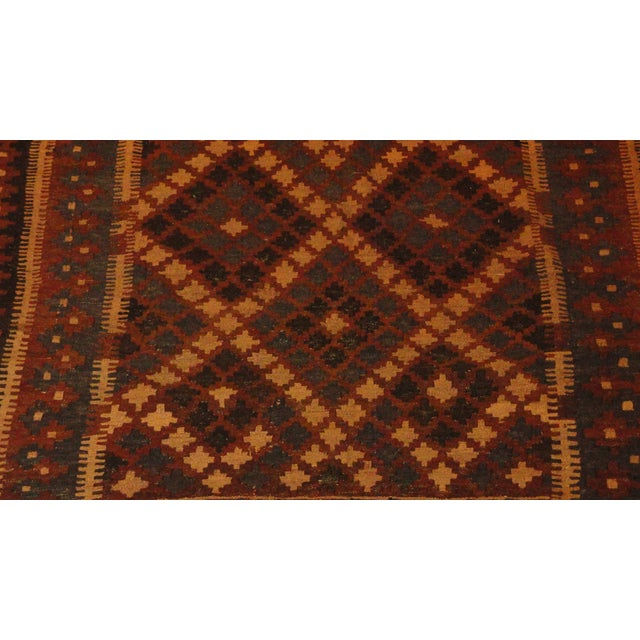 A stunning, very fine, wool pile Afghan Kilim rug. It is hand woven and features gorgeous ornate, geometric detailing in...