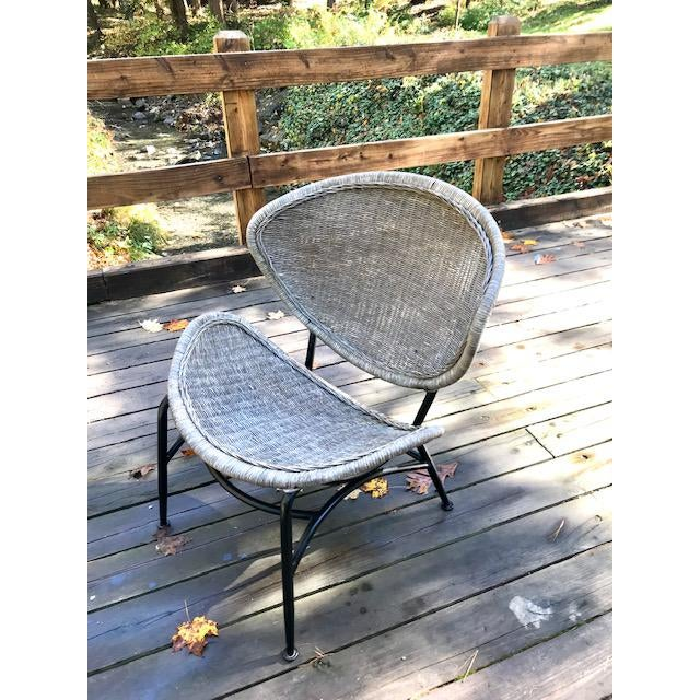 1950's Mid Century Modern Salterini Clam Shell Chair having a wicker seat and back with Rattan strapping. on a black iron...
