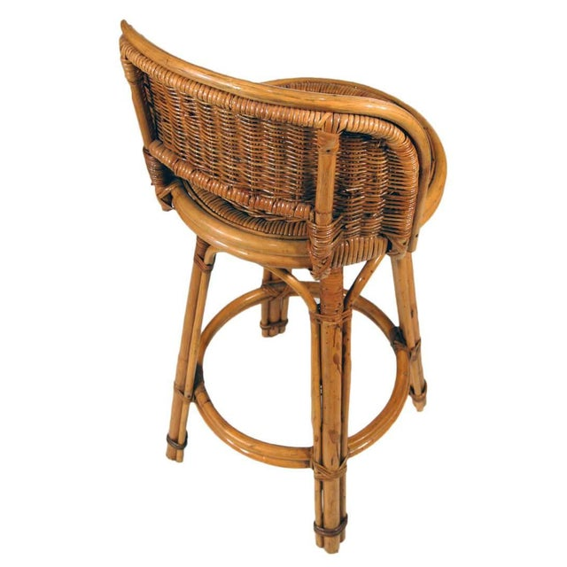 Pair of Rattan bar stools with woven wicker seats and three strand rattan pull legs. Each stool comes with a full formed...
