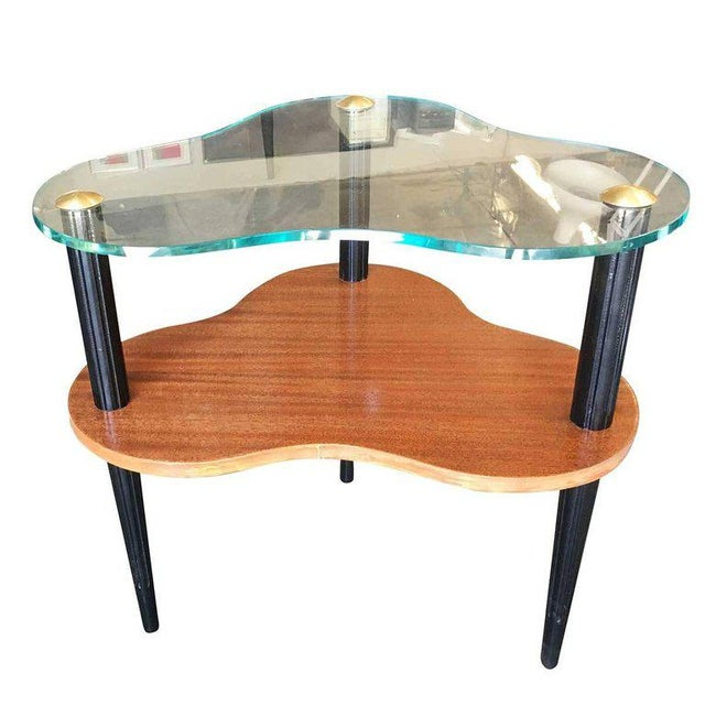 """Gilbert Rohde designed two-tier """"Cloud"""" coffee table. The table has a solid wood base with ebonized legs and outer edge,..."""