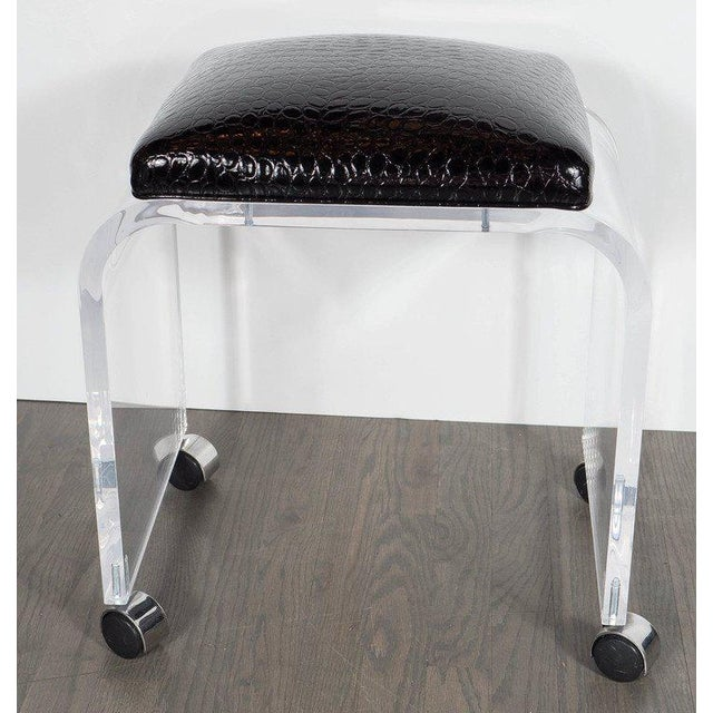 This bench or stool features a thick Lucite design with a waterfall design newly upholstered in a faux black crocodile. It...