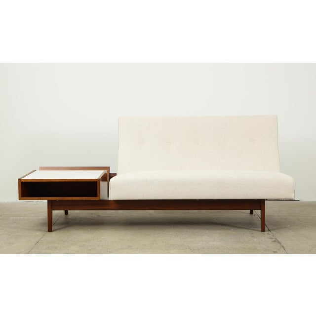 Jens Risom two-seat armless sofa with attached magazine table. The frame is walnut; the magazine table has its original...