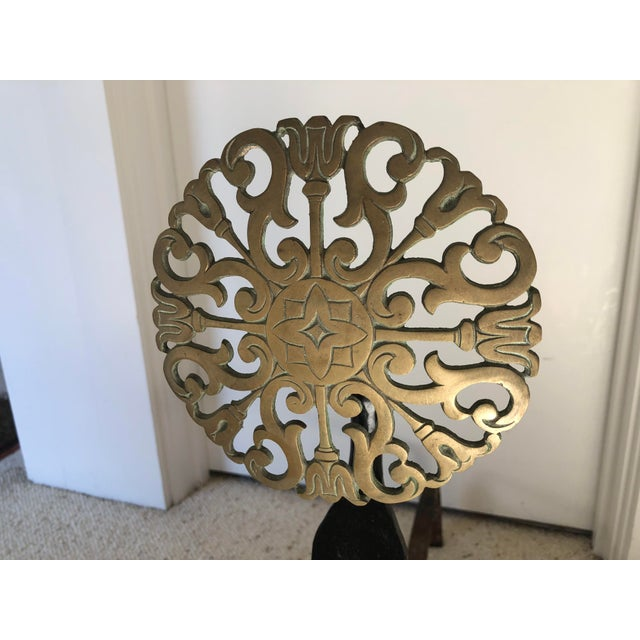 Handsome pair of andirons in cast iron and brass. Brass portion in sunflower motif.