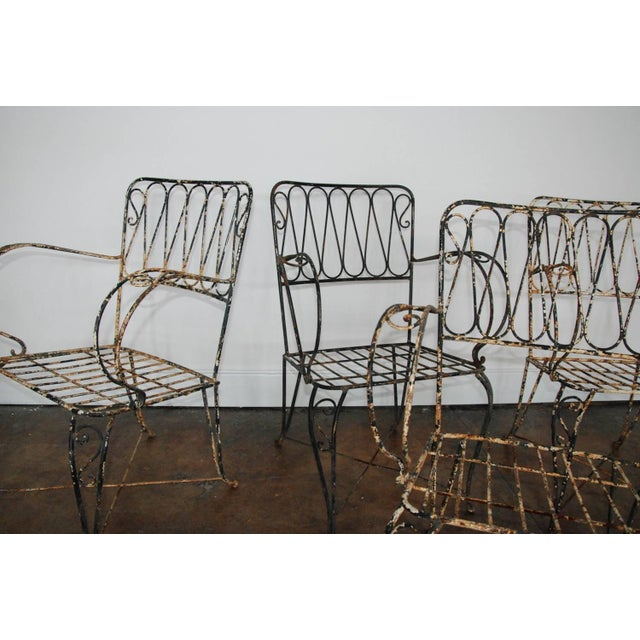 Circa 1940 A fine set of four hand-forged and highly stylized iron garden armchairs that so depicts the French, 1940s...