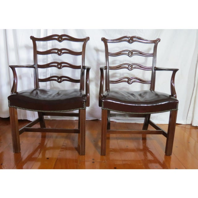 Set of 8 Chippendale mahagony dining chairs featuring carved ribbon ladder backs and upholstered leather seats. The set...