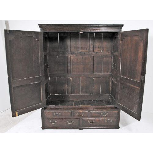 An 18th century English oak cupboard or livery cabinet. The upper section has two doors with the short drawers over a pair...