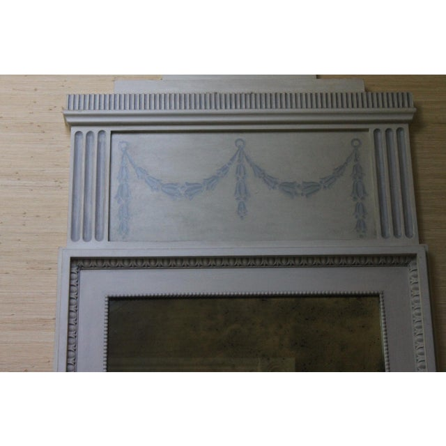 This grayish finished trumeau mirror features the neo classical style of the French King XVI. It is finished and adorned...