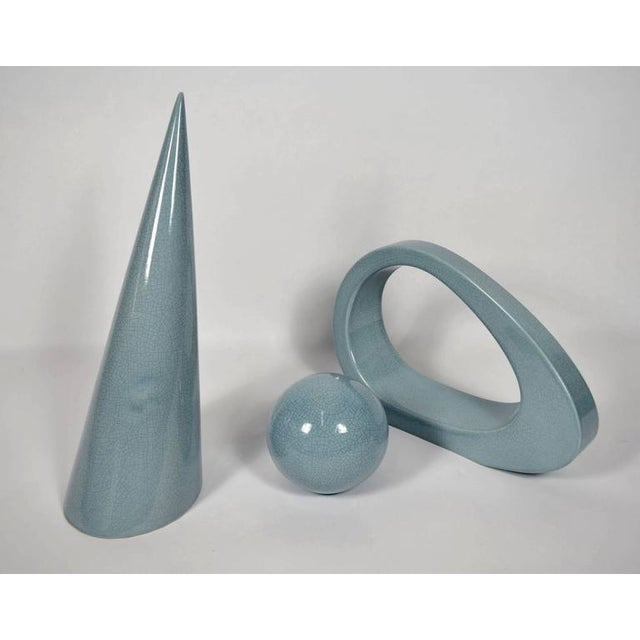 A really nice set of three ceramic pieces by Jaru. Ceramic has a crackle pattern and pieces are a light blue. Cone is...