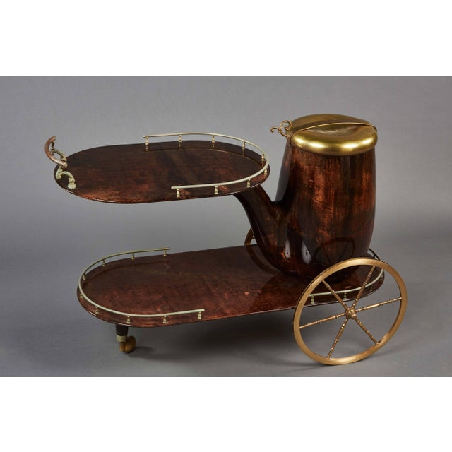 Sheathed in pigmented and lacquered goatskin, with brass appointments and spoked wheels.