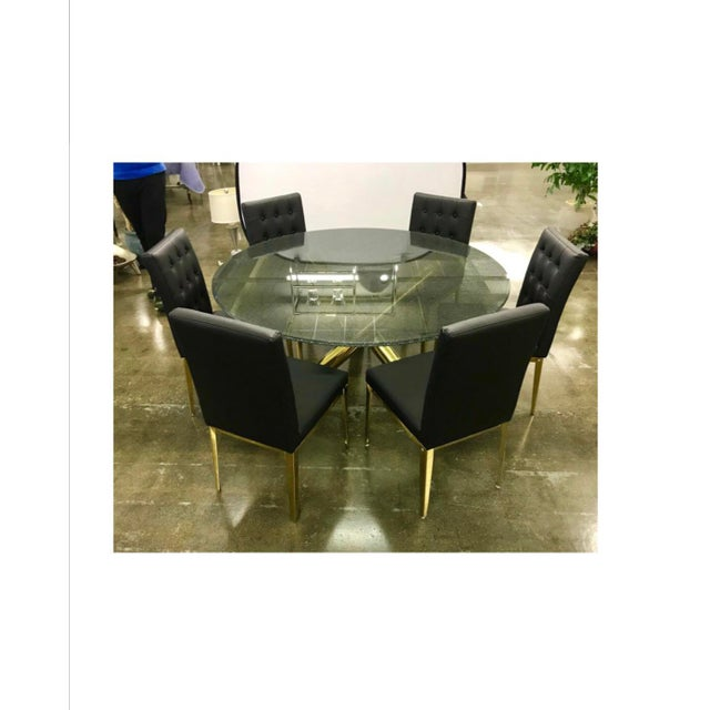 Stunning round crackled glass top table on a brass sculptural base with six matching black leather chairs with brass legs....