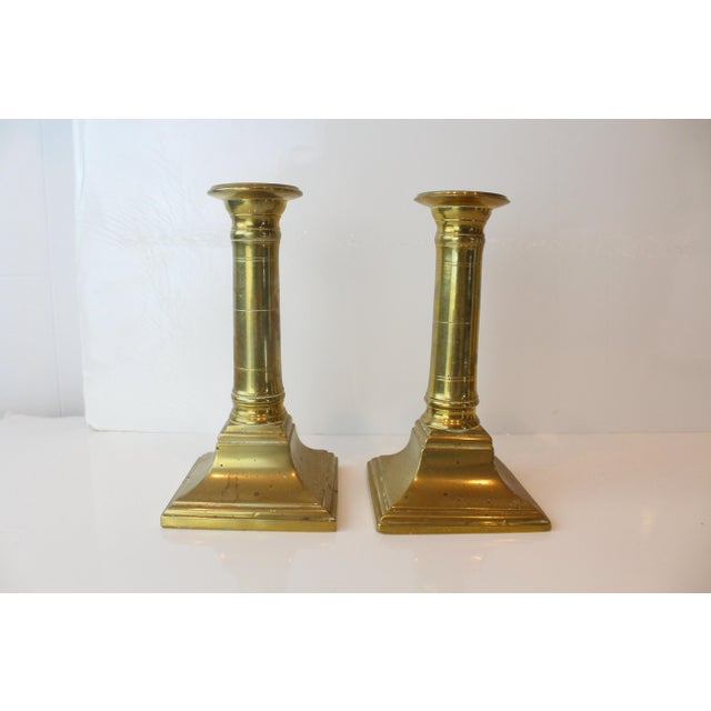 Pair of modern brass candleholders with cut details, square bases, and antique wear.