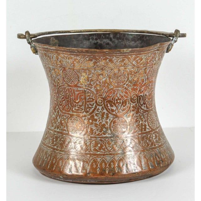 Very large copper bucket with handle. Finely decorated brass repousse in Arabic calligraphy writing and hand-hammered with...