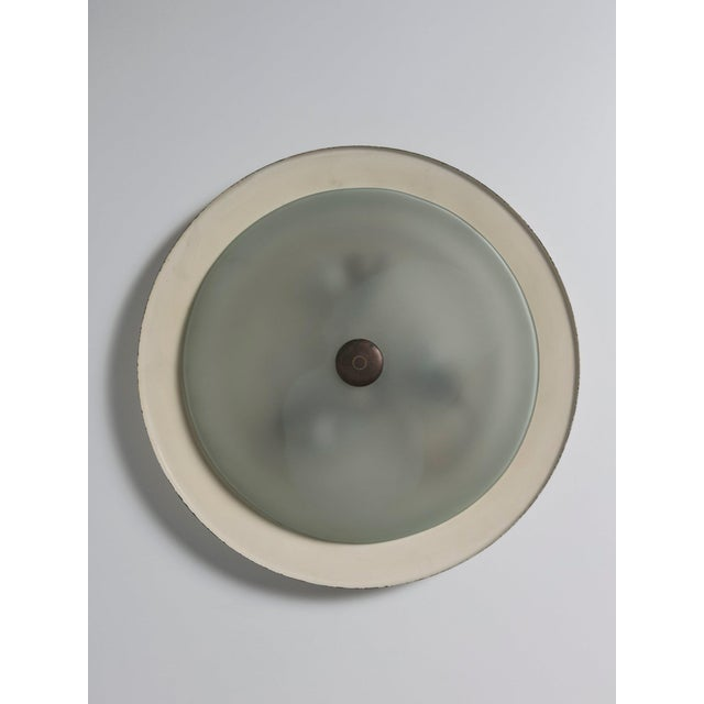 Wall lamp attributed to Fontana Arte. Early Fifties production with large metal disc and frosted glass. Brass details.