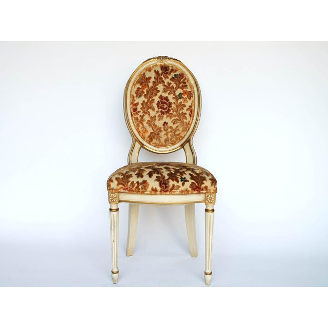 Beautiful side chair with raised floral upholstery, cream colored frame and gold accents. No makers mark. Some wear to...