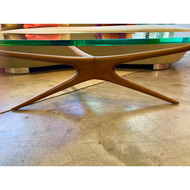 A nice newer bi-morphic glass top coffee table designed by Vladimir Kagan. This table was purchased from Holly Hunt. It is...