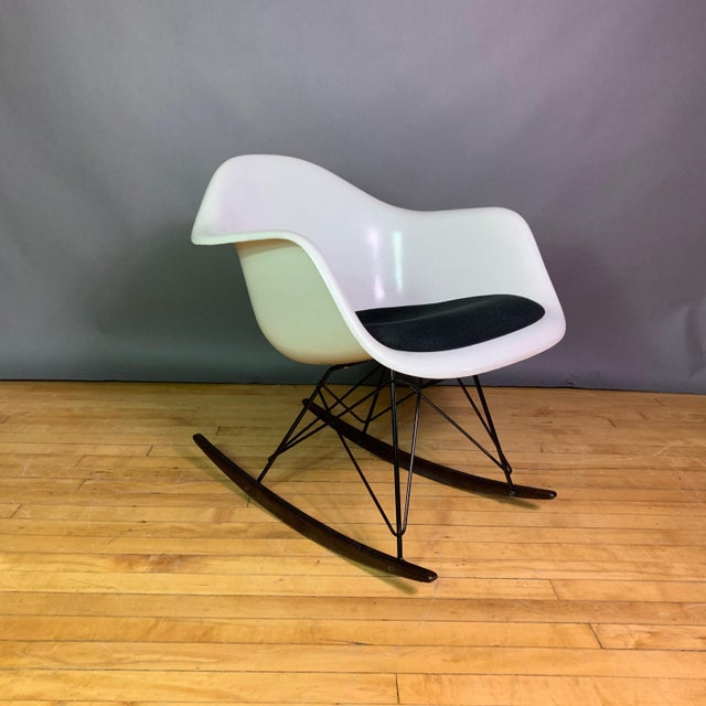 """A mid-century classic by Charles and Ray Eames - the """"RAR"""" rocking chair with dark stained wood rocking skids, frame of..."""