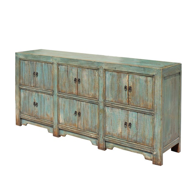 This is a sideboard cabinet table with six storage compartments. It is finished with rustic distressed chalk light pastel...