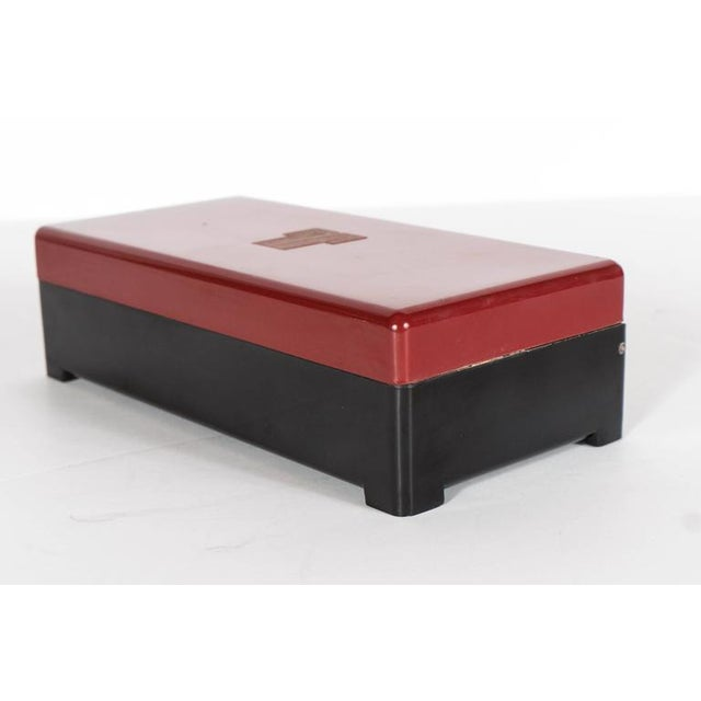 This Machine Age streamlined box features a black bakelite body with a stepped legs and a burgundy top adorned with a...