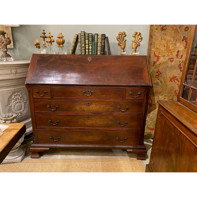 An antique flame mahogany slant front desk with three lower drawers. Opens to reveal a leather writing surface, eight...