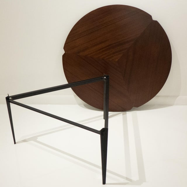 Round cocktail table with tripod enameled steel base. Top is reversible; rosewood on one side, mahogany on the other--both...