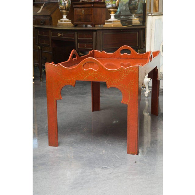 This custom-made tray table is painted in a Chinese or brick red and delicately decorated with a soft gold design. The top...