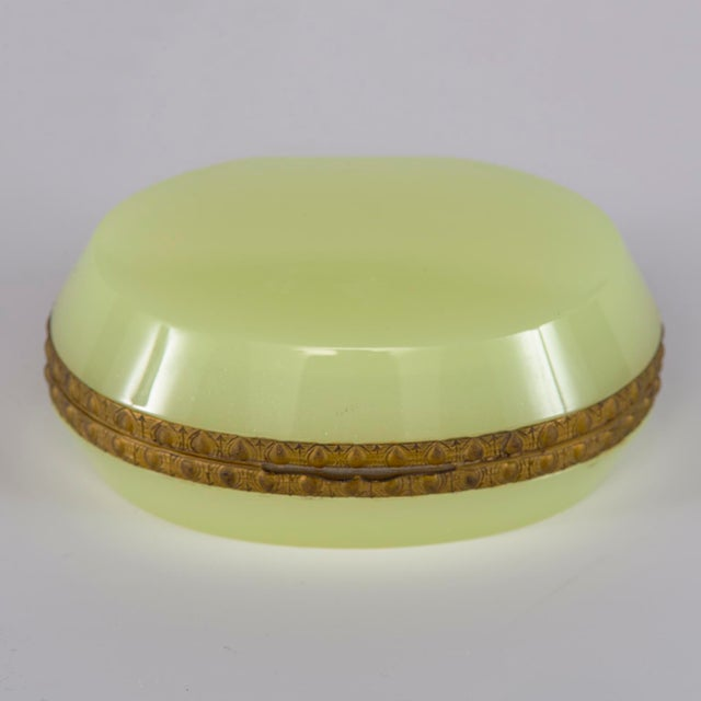 Circa 1920s French uranium opaline glass hinged box is oval shaped with fancy brass trim. Unknown maker