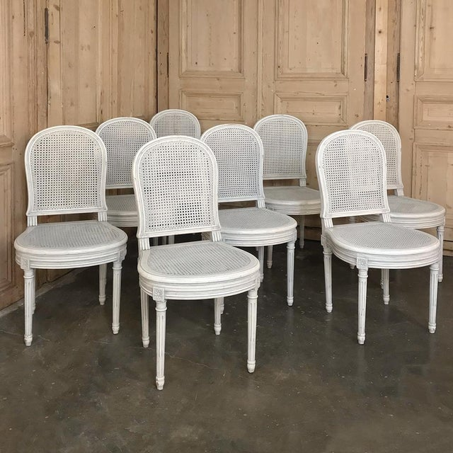 Set of 8 Antique French Louis XVI Painted Dining Chairs feature a patinaed white painted finish and caned back and seats...