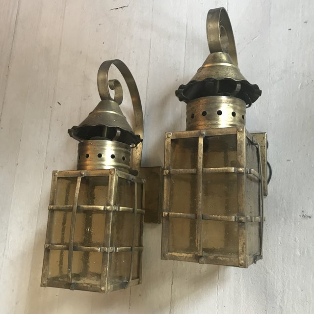 Amber hued panels accent these brass lanterns. The pair is from the 1990s.